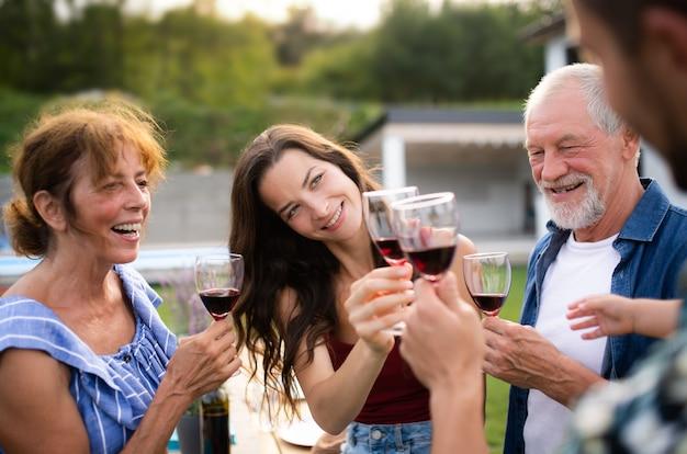 Portret van mensen met wijn buiten op de barbecue van de familietuin, rammelende glazen.
