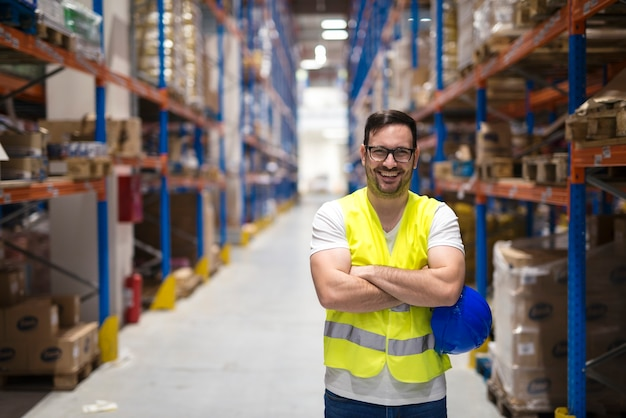 Portret van middelbare leeftijd magazijnmedewerker permanent in groot magazijn distributiecentrum met gekruiste armen