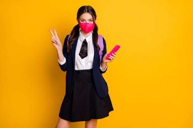 Portret van middelbare school student meisje gebruik smartphone show v-sign