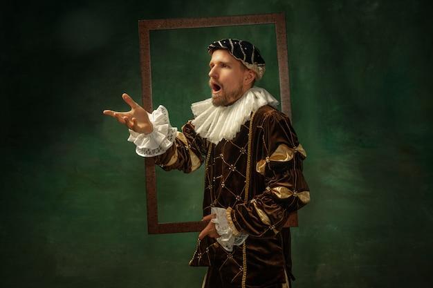 Portret van middeleeuwse jongeman in vintage kleding met houten frame op donkere muur