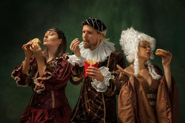 Portret van middeleeuwse jongeren in vintage kleding op donkere muur