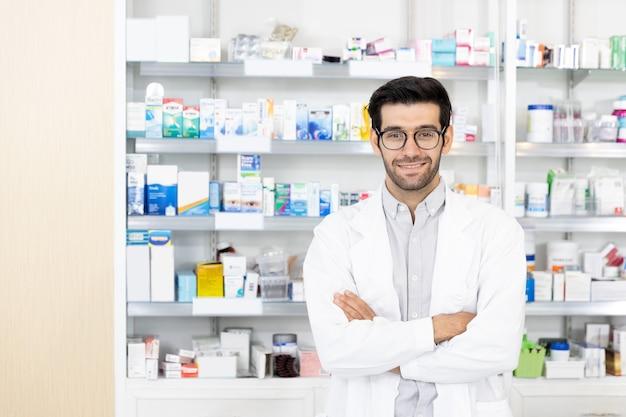 Portret van midden-oosten mannelijke apotheker staande armen gekruist en glimlach camera kijken naar moderne apotheek. bedrijfseigenaar