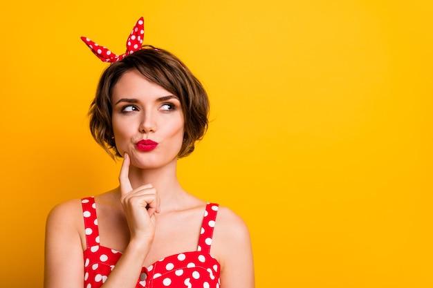 Portret van minded geïnteresseerd meisje kijken copyspace denken gedachten droom beslissen keuze keuze besluit aanraking handen kin dragen stijlvolle kleding geïsoleerd over gele kleur muur