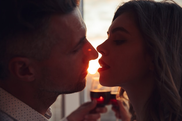 Portret van minnaars die bij zonsondergang kussen en glas met wijn thuis houden