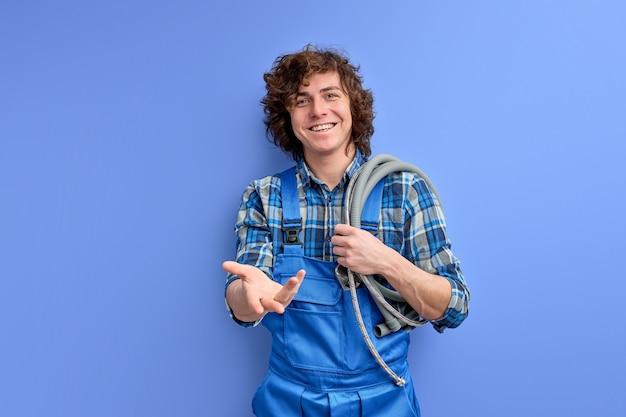 Portret van minzame loodgieter man met slang op schouders klaar om klanten te helpen