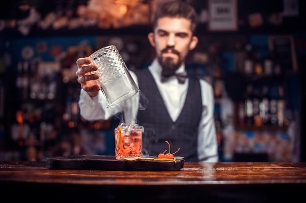 Portret van mixologist verse alcoholische drank in de glazen gieten