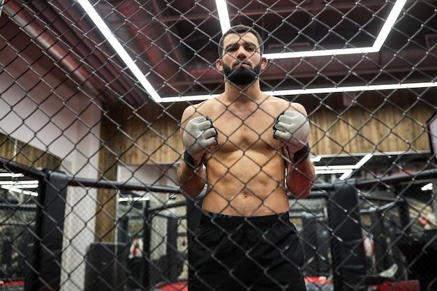 Portret van mma-jager die nadenkt over strategie voor wedstrijd, staande op de ring die zich voorbereidt op gevecht, shirtloze gespierde man gaat vechten oefenen. door kooi geschoten