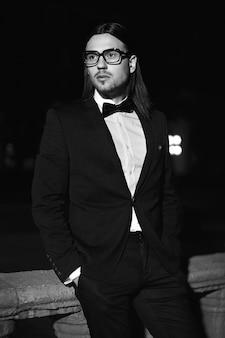 Portret van mode elegante langharige jonge man. aantrekkelijk en knap mannelijk model in zwart pak met snor in de straat 's nachts