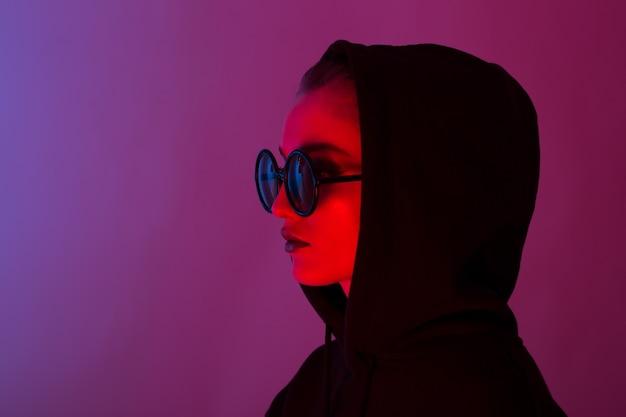 Portret van mode jong meisje in een zwarte trui met een capuchon en ronde zonnebril in rood en blauw neonlicht in de studio.