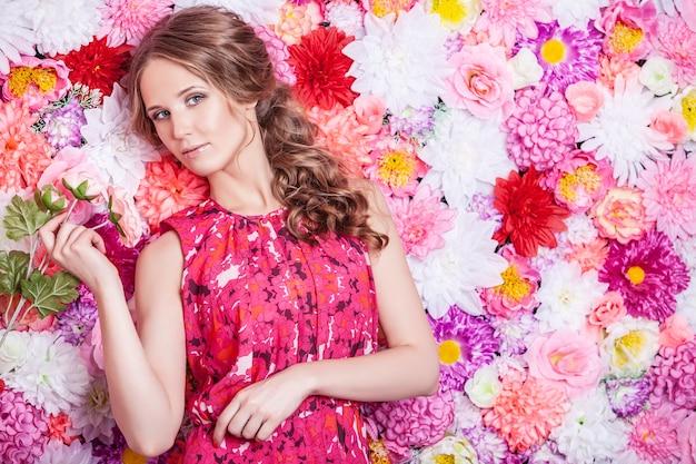 Portret van mode mooie vrouw, lief en sensueel met luxe make-over en haren op de achtergrond kleuren bloemen