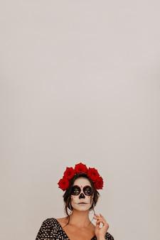 Portret van model tegen witte muur, poseren in kroon van natuurlijke bloemen. halloween-skeletmake-up ziet er ongebruikelijk uit