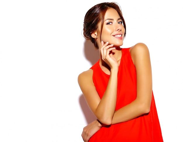 Portret van model van de manier het leuke jonge vrouw in een rode kleding op een witte muur