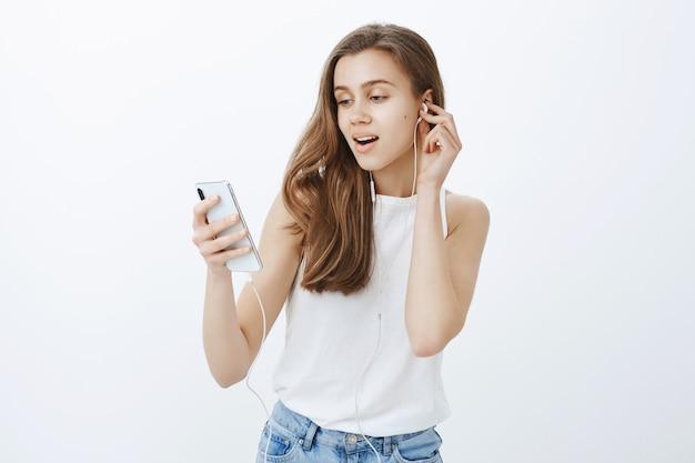 Portret van modern aantrekkelijk meisje zet oortelefoons, luisteren podcast of muziek op mobiele telefoon