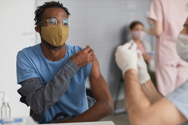 Portret van moderne afro-amerikaanse man die covid-vaccin neemt in vaccinatiecentrum, kopieer ruimte