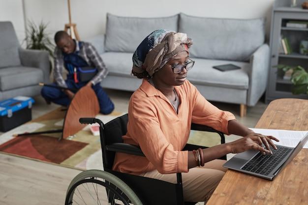 Portret van moderne afro-amerikaanse vrouw die rolstoel gebruikt en vanuit huis werkt met klusjesman die meubels op de achtergrond, service- en assistentieconcept monteert, kopieer ruimte