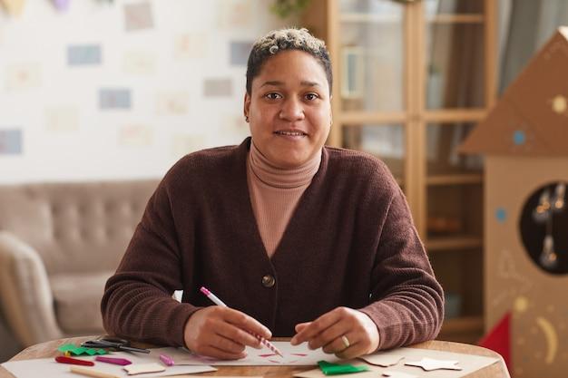 Portret van moderne afro-amerikaanse vrouw glimlachend in de camera tijdens het tekenen van kerstkaarten, kopieer ruimte