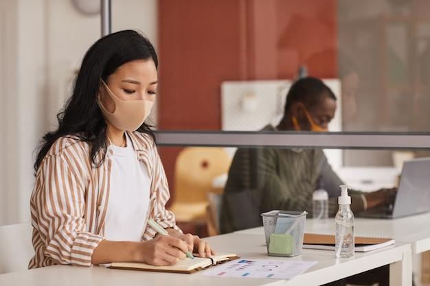 Portret van moderne aziatische onderneemster die masker draagt en in planner schrijft terwijl het werken in bureaucel, exemplaarruimte