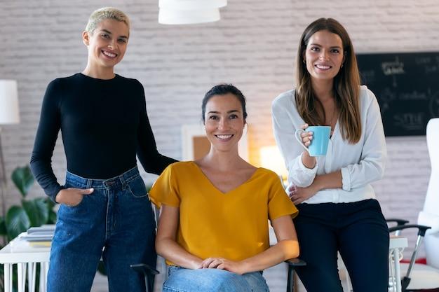 Portret van moderne drie ondernemersvrouwen die naar de camera kijken terwijl ze op kantoor blijven.