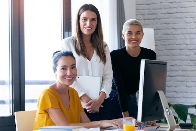 Portret van moderne drie ondernemersvrouwen die naar de camera kijken terwijl ze op kantoor werken.