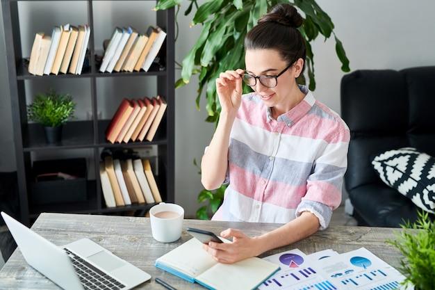 Portret van moderne jonge vrouw die glazen dragen die smartphone gebruiken op het werk, exemplaarruimte