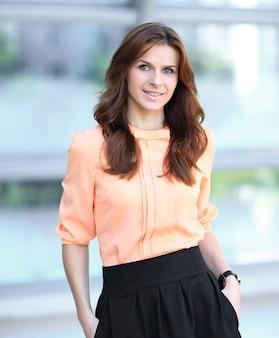 Portret van moderne jonge vrouw op wazig kantoor