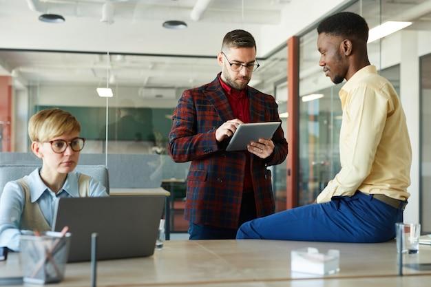 Portret van moderne multi-etnische business team samen te werken aan werkproject in vergaderruimte, focus op bebaarde zakenman met behulp van digitale tablet