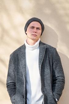 Portret van moderne stedelijke jonge ernstige hipster stijlvolle man met moderne grijze jas, witte trendy trui en zwarte spijkerbroek