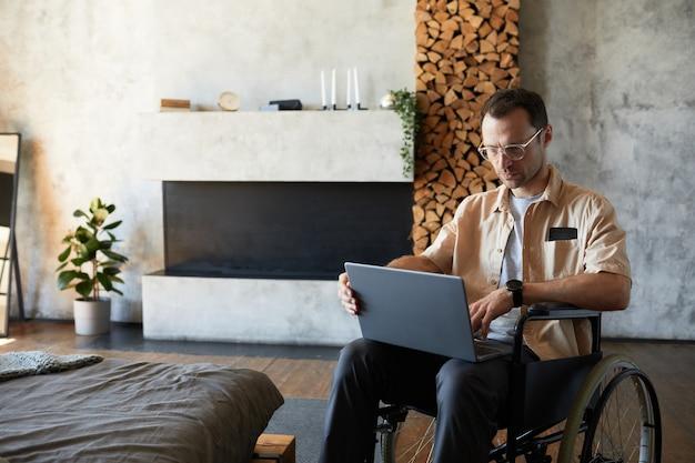Portret van moderne volwassen man in rolstoel met laptop thuis in designer interieur, kopieer ruimte