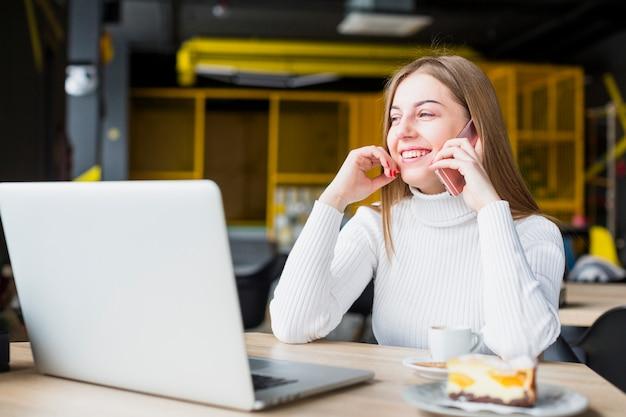 Portret van moderne vrouw die met laptop werkt