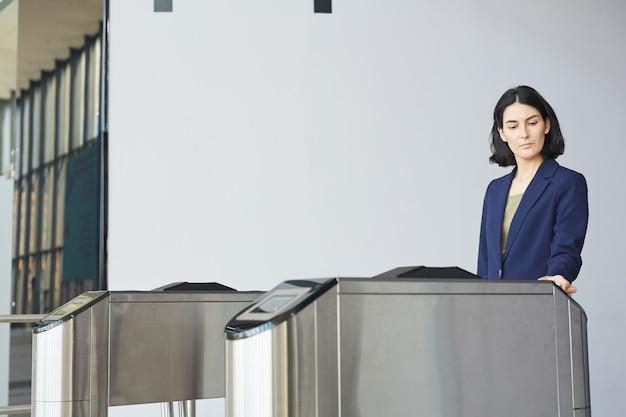 Portret van moderne zakenvrouw uit het midden-oosten kaart tijdens het passeren van tourniquet poort in luchthaven of kantoorgebouw,