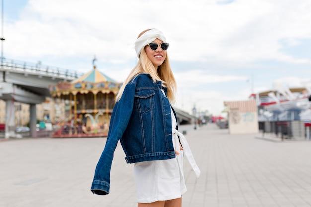 Portret van modieus blondemeisje met gelukkige glimlach die een jasje zwarte stijl buiten in de stad in zonnige zomerdag dragen