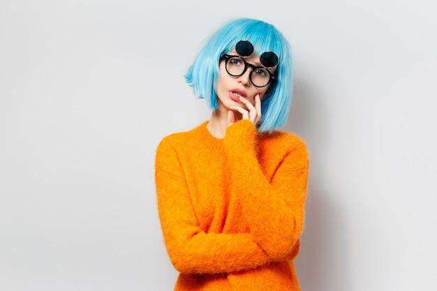 Portret van modieus jong meisje op witte muur. vrouw met blauw kapsel dat ronde zonnebril en oranje sweater draagt.