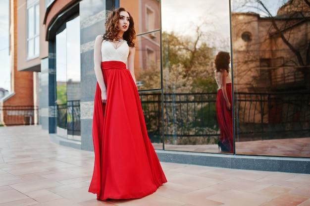 Portret van modieus meisje bij rode avondjurk gesteld achtergrondspiegelvenster van de moderne bouw