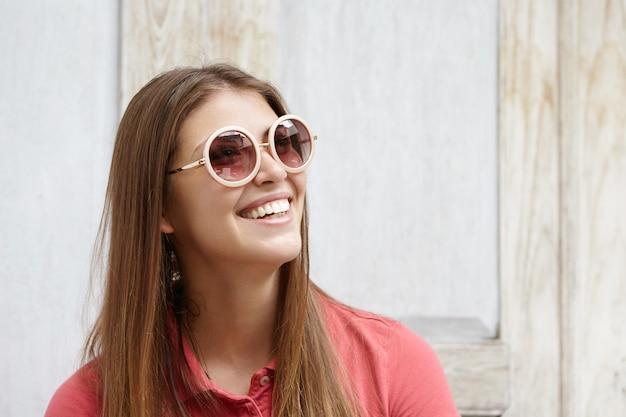 Portret van modieus meisje dat ronde zonnebril met spiegellenzen en poloshirt draagt die met gelukkige glimlach omhoog kijkt, haar witte tanden toont, status geïsoleerd tegen houten muur