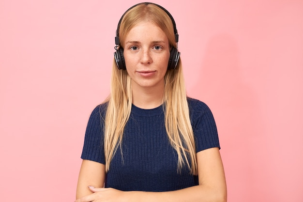Portret van modieus student meisje met neusring poseren op roze in draadloze hoofdtelefoons, luisteren naar online lezing, audioboek of podcast
