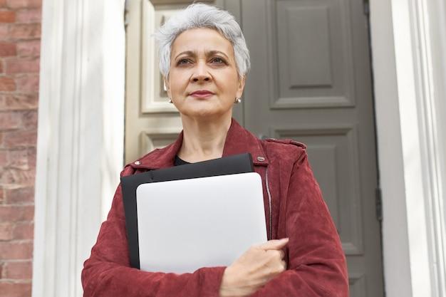 Portret van modieuze 50-jarige blanke vrouw met draagbare computer poseren buiten haar huis