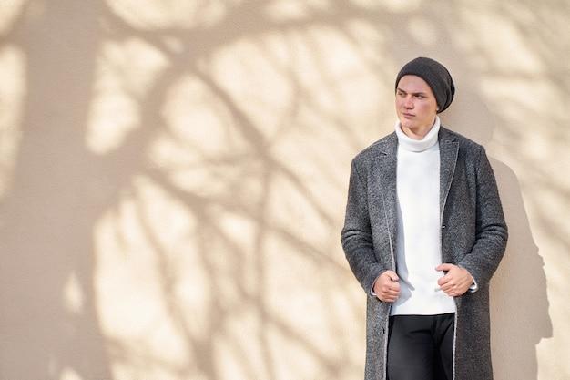 Portret van modieuze aantrekkelijke glimlachende hipster trendy man met een stijlvolle grijze jas, witte trui en zwarte spijkerbroek staan in de buurt van beige muur en wegkijken