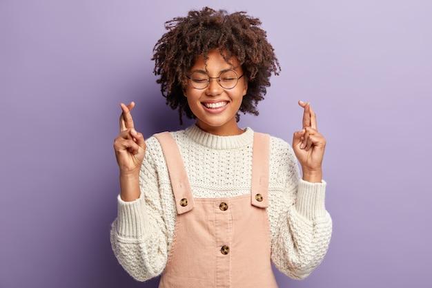 Portret van modieuze afro-amerikaanse vrouw houdt de ogen gesloten van plezier, glimlacht breed, vingers gekruist, gelooft in geluk, vraagt om iets, geïsoleerd over paarse muur. handgebaar