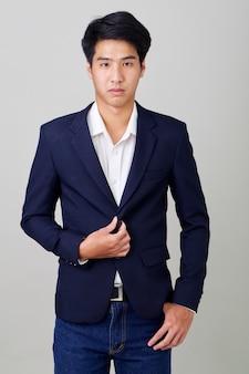 Portret van modieuze aziatische zakenman op helder grijs