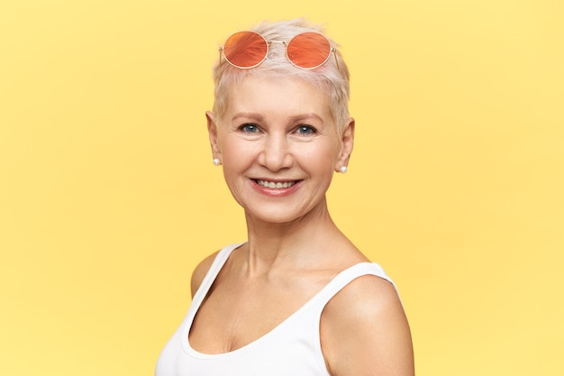 Portret van modieuze blanke vrouwelijke gepensioneerde m / v wandelen op zonnige warme dag dragen ronde roze zonnebril op haar hoofd, camera kijken met een blije glimlach