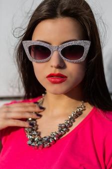 Portret van modieuze brunette vrouw in stijlvolle zonnebril en roze t-shirt close-up.