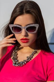 Portret van modieuze brunette vrouw in stijlvolle zonnebril en roze t-shirt close-up