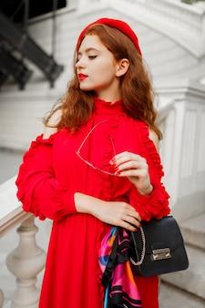 Portret van modieuze gember vrouw in rode baret en elegante jurk poseren buiten.