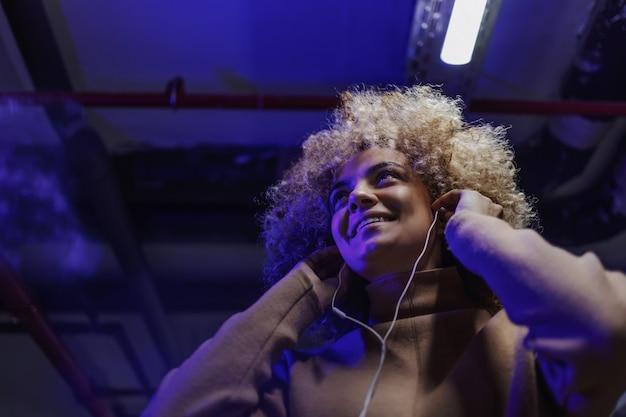 Portret van modieuze glimlachende jonge vrouw met krullend haar, luisteren naar de muziek en wegkijken.
