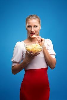 Portret van modieuze jonge blonde vrouw in roze-rode jurk, mooie lippen, lichte make-up houden, eten van gebakken aardappel, friet, chips en poseren over blauwe muur.