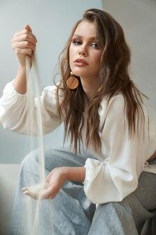 Portret van modieuze jonge mooie vrouw, gekleed in stijlvolle outfit en houten oorbellen zetten zand van de ene hand naar de andere