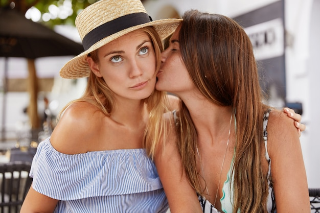 Portret van modieuze jonge vrouwelijke lesbiennes hebben een gepassioneerde kus, hebben goede relaties, tonen ware liefde, recreëren samen tegen het interieur van een buitencafé. homoseksuele relaties concept