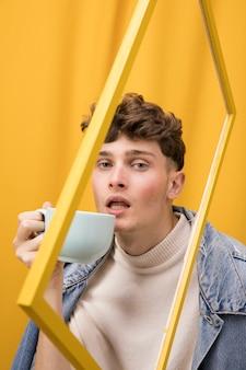 Portret van modieuze jongen drinken in een frame