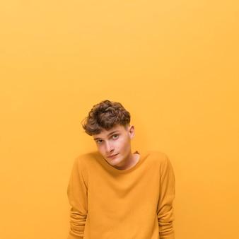 Portret van modieuze jongen tegen gele achtergrond