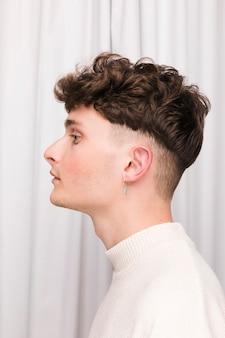 Portret van modieuze jongen voor wit gordijn